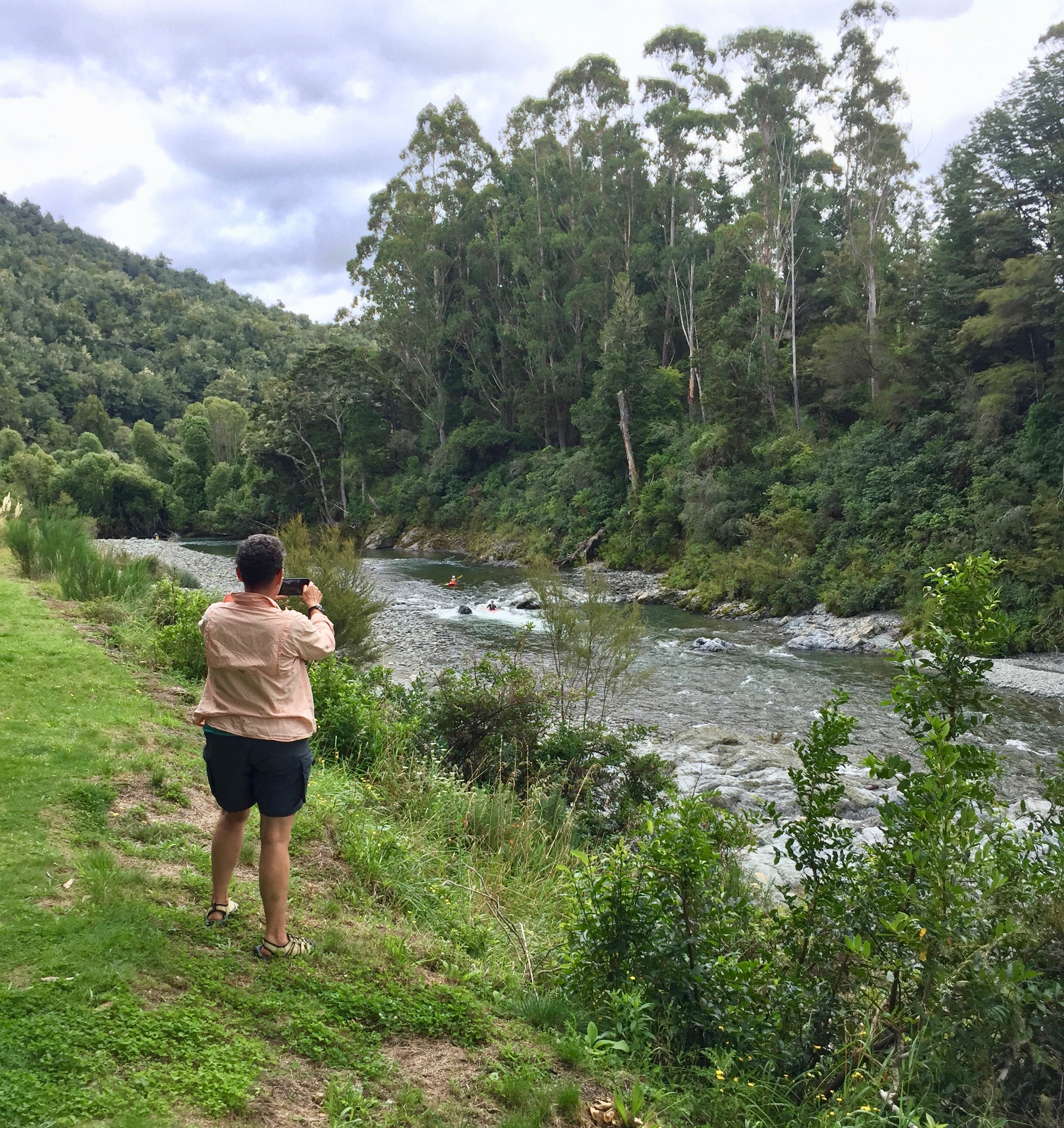 Camille taking a picture of some kayakers  on the Pelorus River